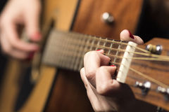 Η νέα γυναίκα στερέωσε με τις σειρές κιθάρων δάχτυλων Στοκ Εικόνα