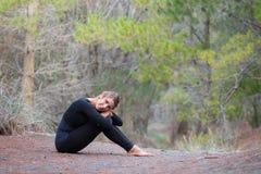 Η νέα γυναίκα στην αθλητική εξάρτηση κάθεται στο έδαφος σε ένα δάσος Στοκ Εικόνες