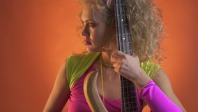 Η νέα γυναίκα στην αναδρομική εξάρτηση θέτει με την κιθάρα, πορτοκαλί υπόβαθρο απόθεμα βίντεο