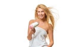 Η νέα γυναίκα στην πετσέτα ξεραίνει την τρίχα ένα hairdryer Στοκ φωτογραφία με δικαίωμα ελεύθερης χρήσης