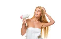 Η νέα γυναίκα στην πετσέτα ξεραίνει την τρίχα ένα hairdryer Στοκ εικόνα με δικαίωμα ελεύθερης χρήσης