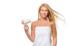 Η νέα γυναίκα στην πετσέτα ξεραίνει την τρίχα ένα hairdryer Στοκ φωτογραφίες με δικαίωμα ελεύθερης χρήσης