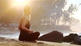 Η νέα γυναίκα στη μαύρη φόρμα γυμναστικής κάνει τη γιόγκα στην αμμώδη παραλία φιλμ μικρού μήκους