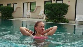 Η νέα γυναίκα στη χαλάρωση γυαλιών ηλίου και κολυμπά αργά στην πισίνα φιλμ μικρού μήκους