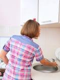 Η νέα γυναίκα στο αμερικανικό πουκάμισο ύφους καθαρίζει τον πίνακα στοκ εικόνα με δικαίωμα ελεύθερης χρήσης