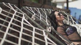Η νέα γυναίκα στο ασημένιο κοστούμι swimmimg κάνει ηλιοθεραπεία την τοποθέτηση στο κρεβάτι σχοινιών Ελεύθερος χρόνος της χαριτωμέ φιλμ μικρού μήκους