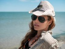 Η νέα γυναίκα στο καπέλο, τα γυαλιά ηλίου και το πουκάμισο κάθεται στην παραλία του ωκεανού, θάλασσα στο ηλιόλουστο γέλιο γυναικώ στοκ εικόνα