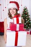 Η νέα γυναίκα στο καπέλο santa με το σωρό παρουσιάζει κοντά στα Χριστούγεννα TR Στοκ Εικόνα
