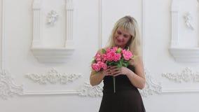 Η νέα γυναίκα στο καφετί φόρεμα κρατά τα ρόδινα λουλούδια φιλμ μικρού μήκους