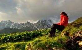 Η νέα γυναίκα στο κόκκινο σακάκι απολαμβάνει το ηλιοβασίλεμα στα βουνά Στοκ φωτογραφία με δικαίωμα ελεύθερης χρήσης