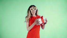 Η νέα γυναίκα στο κόκκινο φόρεμα με τα αστεία γυαλιά χορεύει σε ένα πράσινο υπόβαθρο απόθεμα βίντεο