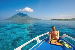 Η νέα γυναίκα στο μαγιό κάθεται στη βάρκα στην ηλιόλουστη ημέρα κοιτάζοντας σε ένα CL Στοκ φωτογραφία με δικαίωμα ελεύθερης χρήσης