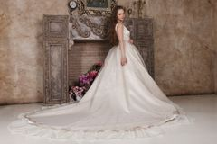 3912247fc91d Η νέα γυναίκα στο μακρύ φόρεμα θέτει κοντά στην πλαστή εστία στοκ εικόνες
