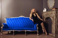 Η νέα γυναίκα στο μαύρο φόρεμα κάθεται στον μπλε καναπέ κοντά στην εστία στοκ εικόνες