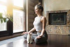 Η νέα γυναίκα στο μισό Lotus θέτει στο σπίτι με τη γάτα Στοκ Φωτογραφίες