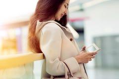 Η νέα γυναίκα στο μπεζ παλτό χρησιμοποιεί το κοινωνικό δίκτυο app, τρόπος ζωής Πολυ-εθνικό κορίτσι Στοκ Εικόνα
