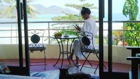 Η νέα γυναίκα στο μπουρνούζι κάθεται σε έναν καφέ κατανάλωσης μπαλκονιών και χρησιμοποιεί το κινητό τηλέφωνο στην καταπληκτική άπ φιλμ μικρού μήκους