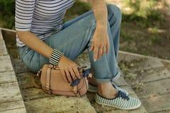 83eaa2b0be9 Η νέα γυναίκα στο τζιν παντελόνι, ριγωτά πάνινα παπούτσια κάθεται στο  παλαιό ξύλινο s στοκ