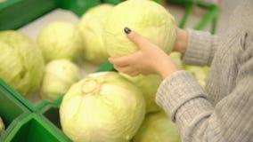 Η νέα γυναίκα στο φυτικό τμήμα μιας υπεραγοράς επιλέγει ένα λάχανο απόθεμα βίντεο