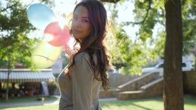 Η νέα γυναίκα στο φόρεμα πηγαίνει με τα ζωηρόχρωμα μπαλόνια στο backlight και το χαμόγελο στο πάρκο, ευτυχείς συγκινήσεις φιλμ μικρού μήκους