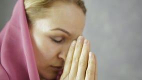 Η νέα γυναίκα στο headscarf προσεύχεται θηλυκά χέρια κινηματογραφήσεων σε πρώτο πλάνο που κρατούν την αλυσίδα με έναν σταυρό απόθεμα βίντεο