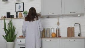 Η νέα γυναίκα στο nightie προετοιμάζει το πρόγευμα στην κουζίνα το πρωί φιλμ μικρού μήκους