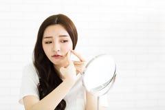 Η νέα γυναίκα συμπιέζει την ακμή της μπροστά από τον καθρέφτη Στοκ Φωτογραφία