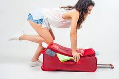 Η νέα γυναίκα συσκευάζει τα πράγματά της, ντύνει στις πλήρεις αποσκευές Στοκ φωτογραφία με δικαίωμα ελεύθερης χρήσης