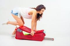 Η νέα γυναίκα συσκευάζει τα πράγματά της, ντύνει στις πλήρεις αποσκευές Στοκ Εικόνες