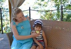 Η νέα γυναίκα ταΐζει τη 3χρονη κόρη με το μήλο υπαίθρια Στοκ Εικόνες