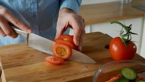 Η νέα γυναίκα τεμαχίζει τις ντομάτες με ένα μαχαίρι για την κατασκευή της σαλάτας σε έναν ξύλινο τέμνοντα πίνακα απόθεμα βίντεο