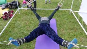 Η νέα γυναίκα τεντώνει το σώμα στις συσκευές κατάρτισης στο πάρκο υπαίθρια φιλμ μικρού μήκους