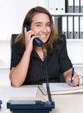 Η νέα γυναίκα τηλεφωνά στο γραφείο Στοκ εικόνα με δικαίωμα ελεύθερης χρήσης