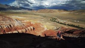 Η νέα γυναίκα τουριστών αναρριχείται σε ένα κόκκινο βουνό πετρών στην ηλιόλουστη ημέρα Υπάρχει φυσικό τοπίο και νεφελώδης ουρανός απόθεμα βίντεο