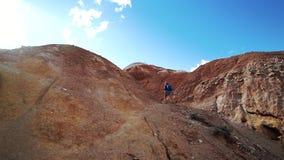 Η νέα γυναίκα τουριστών αναρριχείται σε ένα κόκκινο βουνό πετρών στην ηλιόλουστη ημέρα υποστηρίξτε την όψη απόθεμα βίντεο