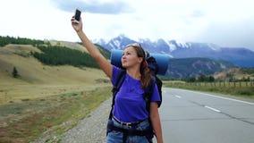 Η νέα γυναίκα τουριστών με ένα σακίδιο πλάτης και τα γυαλιά ηλίου προσπαθεί να πιάσει το τηλεφωνικό σήμα σε έναν δρόμο βουνών Υπά φιλμ μικρού μήκους