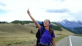 Η νέα γυναίκα τουριστών με ένα σακίδιο πλάτης και τα γυαλιά ηλίου προσπαθεί να πιάσει το τηλεφωνικό σήμα σε έναν δρόμο βουνών Υπά απόθεμα βίντεο