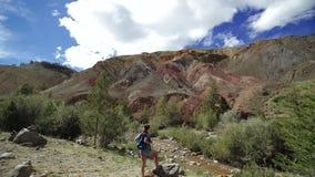 Η νέα γυναίκα τουριστών στέκεται στο κόκκινο βουνό πετρών στην ηλιόλουστη ημέρα Ο ήλιος λάμπει slider απόθεμα βίντεο