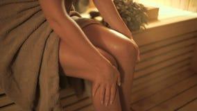 Η νέα γυναίκα τρίβει το πόδι του με το πετρέλαιο στη σάουνα απόθεμα βίντεο