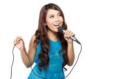Η νέα γυναίκα τραγουδά mic, που απομονώνεται το κράτημα στοκ εικόνες