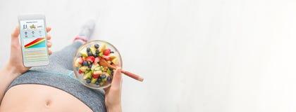 Η νέα γυναίκα τρώει μια σαλάτα φρούτων και χρησιμοποιεί μια ικανότητα app στο smartphone της Στοκ Φωτογραφία