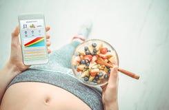 Η νέα γυναίκα τρώει μια σαλάτα φρούτων και χρησιμοποιεί μια ικανότητα app στο smartphone της Στοκ φωτογραφίες με δικαίωμα ελεύθερης χρήσης