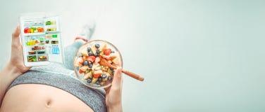 Η νέα γυναίκα τρώει μια σαλάτα φρούτων και χρησιμοποιεί μια ικανότητα app στο smartphone της μετά από ένα workout Στοκ φωτογραφία με δικαίωμα ελεύθερης χρήσης