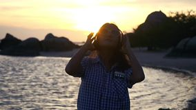 Η νέα γυναίκα φορά τα ακουστικά έχει τη μουσική ακούσματος διασκέδασης στην παραλία στο καταπληκτικό ηλιοβασίλεμα σε σε αργή κίνη απόθεμα βίντεο