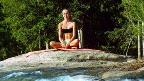 Η νέα γυναίκα χαλαρώνει σε θέση το μισό Lotus από το foamy ποταμό απόθεμα βίντεο