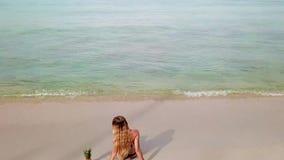 Η νέα γυναίκα χαλαρώνει στην παραλία απόθεμα βίντεο