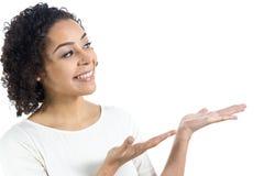 Η νέα γυναίκα χαμογελά και παρουσιάζει κάτι Στοκ φωτογραφίες με δικαίωμα ελεύθερης χρήσης
