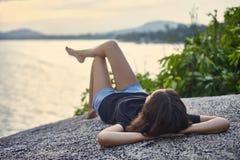 Η νέα γυναίκα χαλαρώνει στο δύσκολο απότομο βράχο και απόλαυση της θέας Στοκ φωτογραφία με δικαίωμα ελεύθερης χρήσης