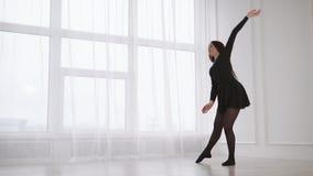 Η νέα γυναίκα χορευτών θερμαίνει τους μυς της πλάτης και παραδίδει μια αίθουσα φιλμ μικρού μήκους