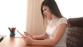 Η νέα γυναίκα χρησιμοποιεί έναν υπολογιστή ταμπλετών απόθεμα βίντεο